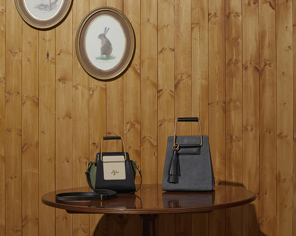A still life fall winter campaign image of handbags with hard light
