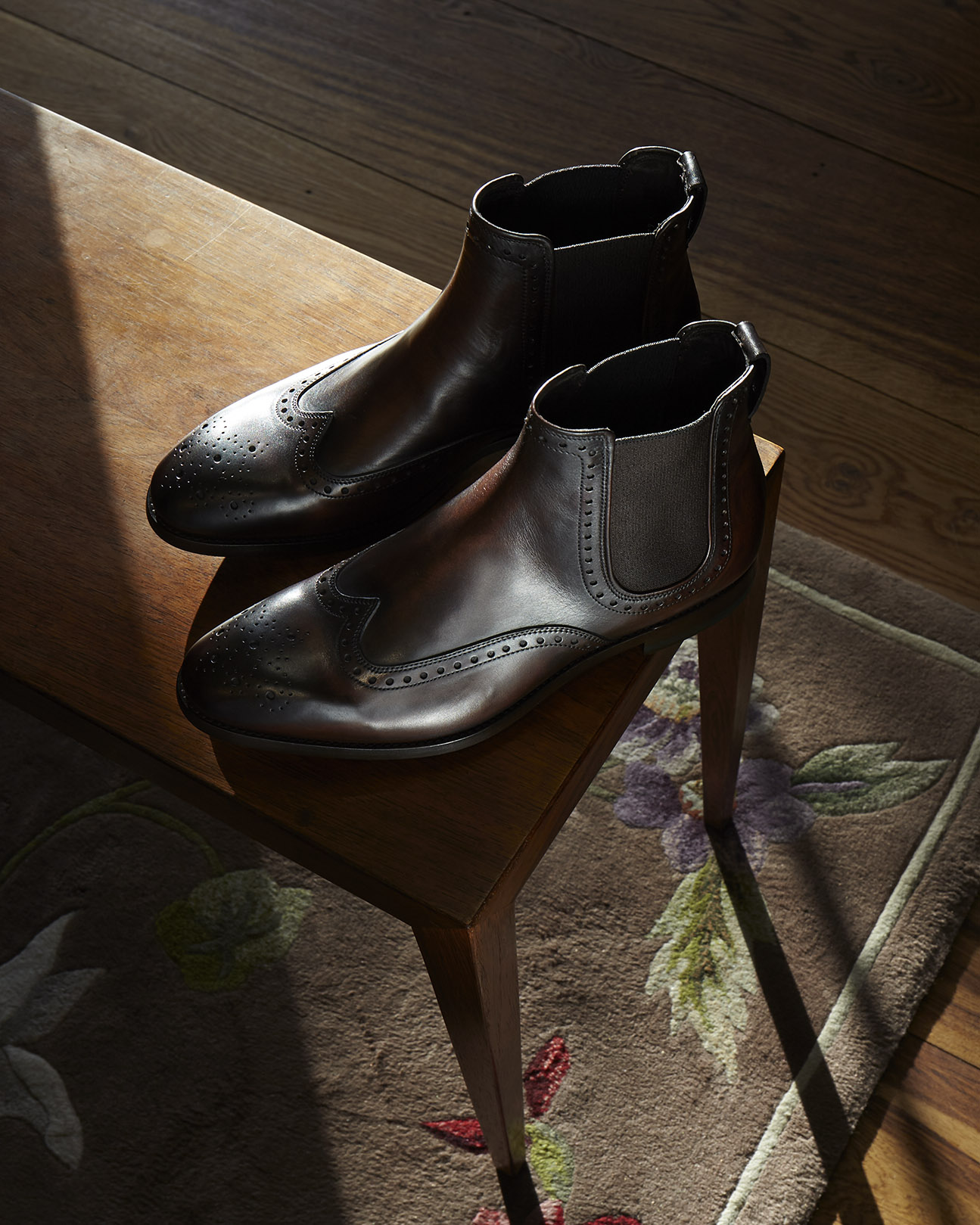A still life image of Paul Smith boots with hard window light