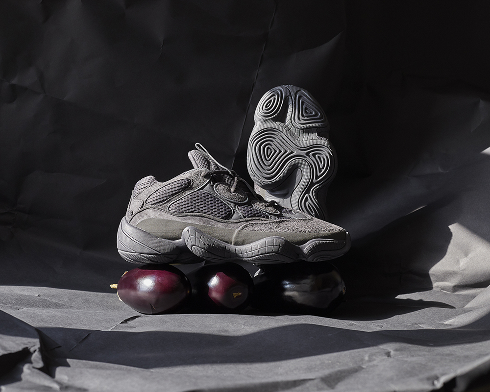 A still life image of adidas trainers sat on top of fruit with hard window light